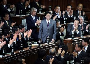 Shinzo Abe, president of the Liberal Democratic Party (LDP), is applauded after being elected Japan's prime minister at the lower house of parliament in Tokyo, Japan, on Wednesday, Dec. 26, 2012. Japan's lower house confirmed Abe as the nation's seventh prime minister in six years, returning him to the office he left in 2007 after his party regained power in a landslide election victory last week. Photographer: Haruyoshi Yamaguchi/Bloomberg *** Local Caption *** Shinzo Abe